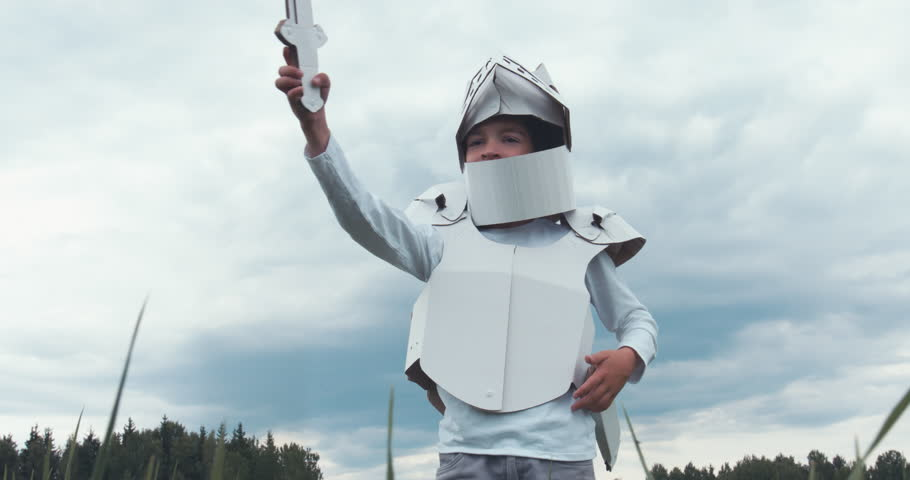 Kid boy wearing cardboard medieval knight armor costume draws a sword from a scabbard against blue sky. 4K UHD 60 FPS SLO MO
