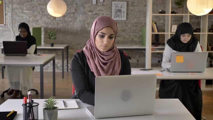 Three young muslim womans in hijab sitting and working in modern office, muslim beautiful woman looking in camera and smiling