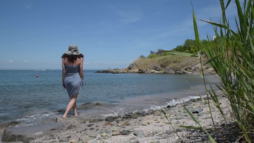 Caucasian curly woman with sarong and hat walking on a beach | Shutterstock HD Video #1012360214
