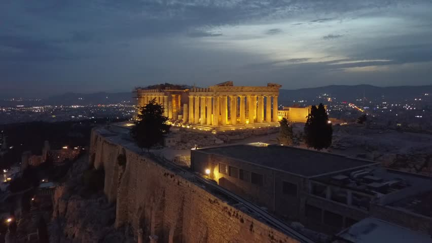 Athens Acropolis and Parthenon in evening at sunset. beautifully lit up. Aerial 4k drone view from above the Greek capital. City center in background. 4k view in low light.