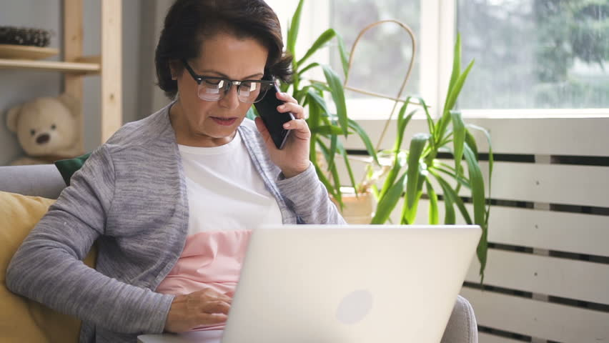 Mature businesswoman is talking on phone, using laptop in home interior, elegant female in glasses is having business dialogue, looking at pc screen, sitting on soft sofa in cozy house. Concept | Shutterstock HD Video #1012372736