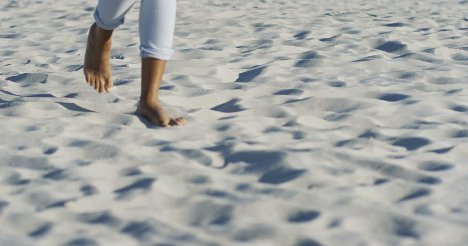 Close up of the African American female barefeet woman walking on the sand on a sunny day. Outside.