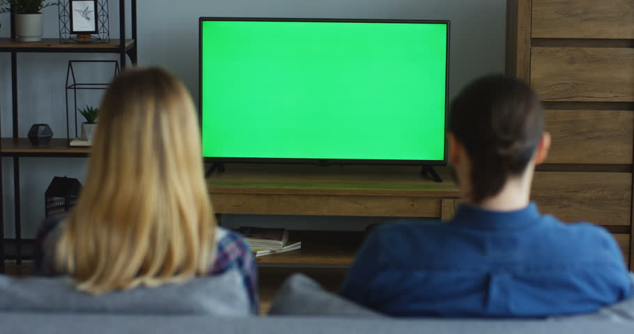Rear of the young woman and man sitting on the couch in the living room and watching TV with green screen, woman talking and waving hands. Chroma key. Indoor | Shutterstock HD Video #1012385393