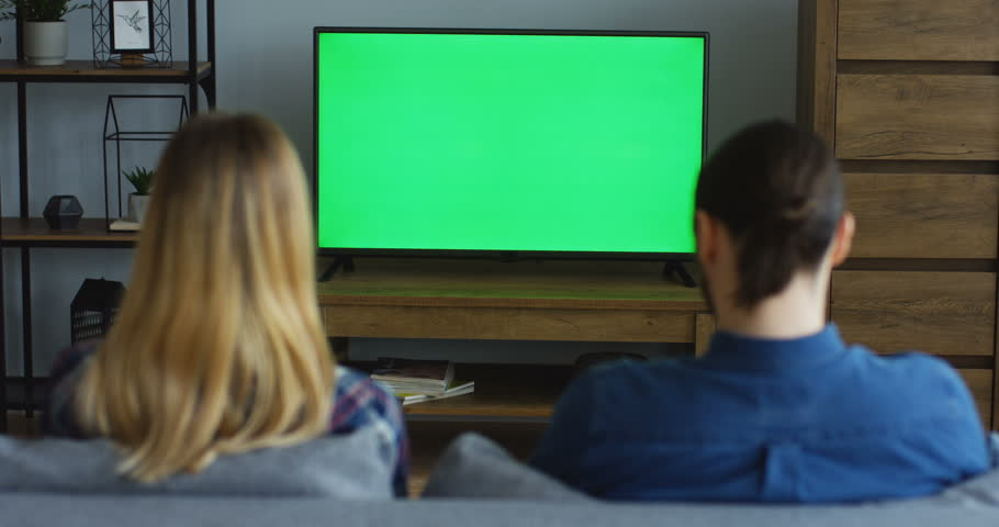 Back view on the blonde woman and man sitting on the sofa in the living room and watching TV with green screen, then changing channels with a remote control. Chroma key. Inside | Shutterstock HD Video #1012385396