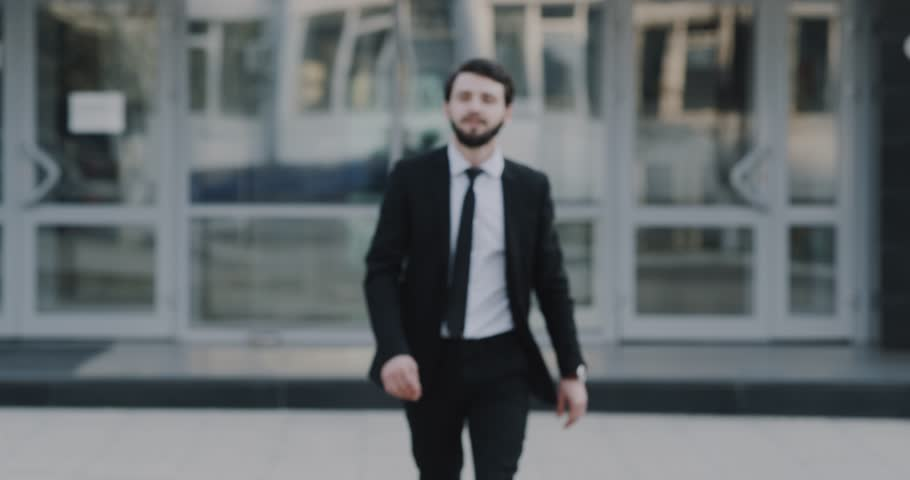 Young businessman walking straight to the camera and smiling, then standing and happy looking to the camera, background business center. #1012389680
