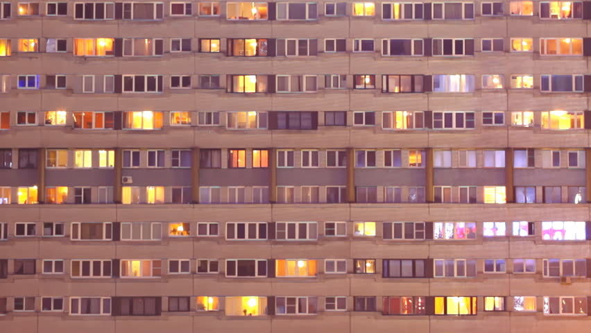 Blinking lights in the windows of apartment building at night timelapse