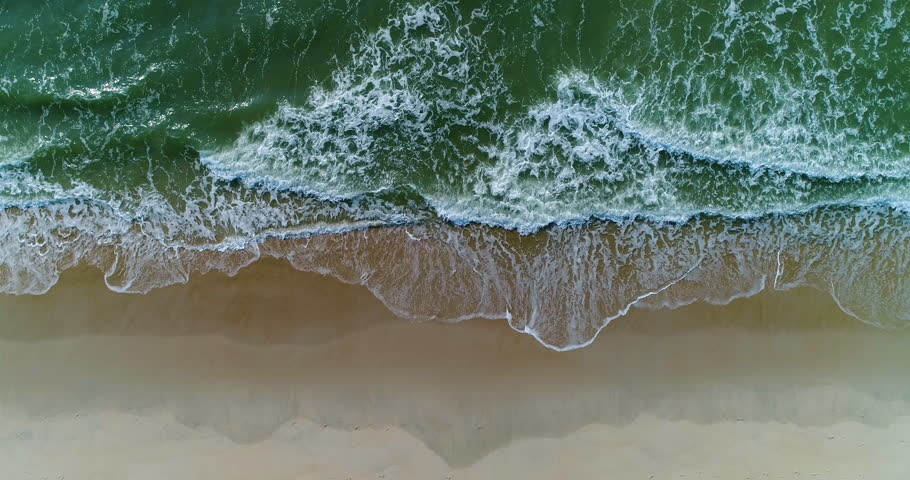 Beautiful 4K tropical beach aerial - a bird's eye view of ocean waves crashing against an empty beach from above #1012392044