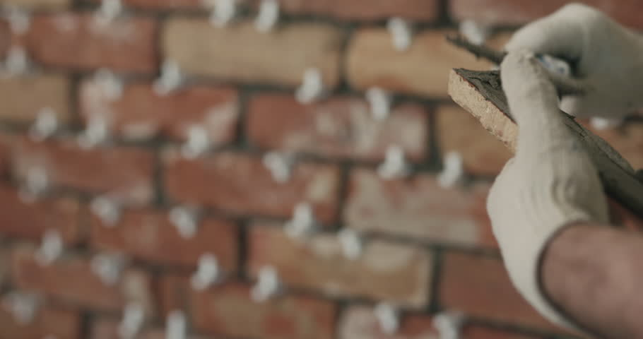 Slow motion closeup worker applying concrete glue to brick tile | Shutterstock HD Video #1012397810