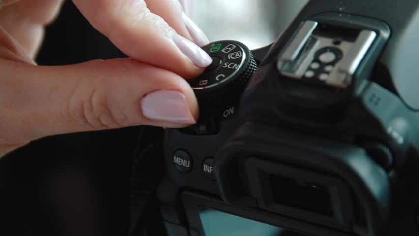 Hand holding and setting up a digital SLR camera. Close up of photographer hands on a photo camera on the set ot production shoot. | Shutterstock HD Video #1012398593