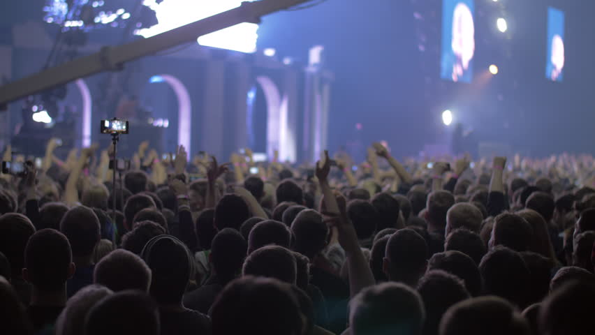 Slow motion shot of fans crowd with hands up and blinking stage lights at the music concert #1012408904