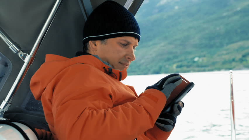 Focused smiling male tourist sitting in cabin of the yacht, writes a message using smartphone