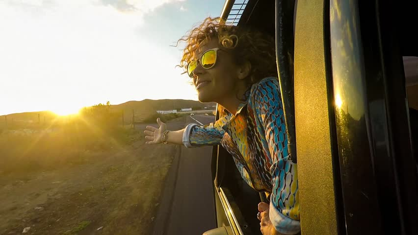 Happy beautiful young woman traveling in a car across the world looking at the road and the destination. dreamer and cheerful nice female concept travel tenerife under the sun at the sunset