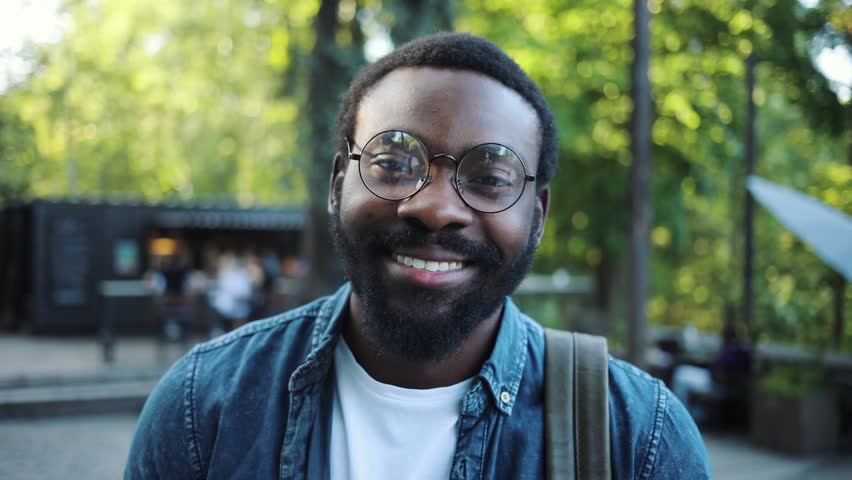 Portrait of young african american man with beard glasses looking at camera smile feel happy close up afro happiness fashion people face sun art handsome attractive slow motion urban outdoor | Shutterstock HD Video #1012437275