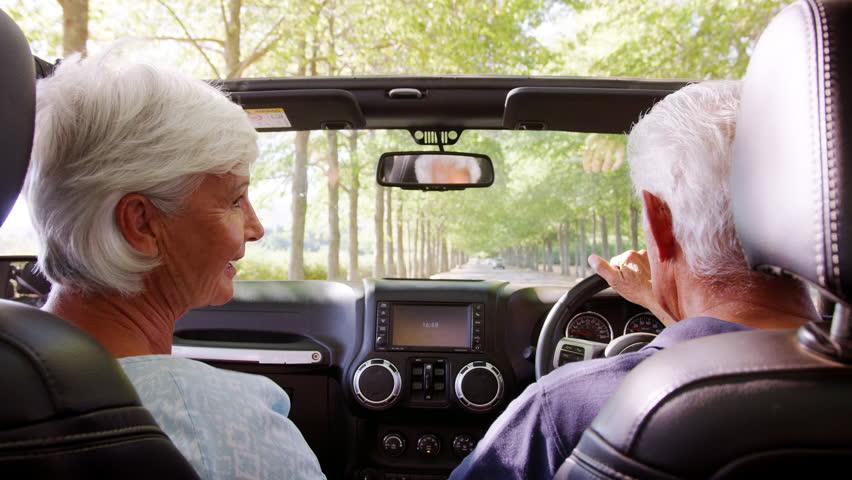 Rear passenger POV of senior couple driving an open top car #1012449341