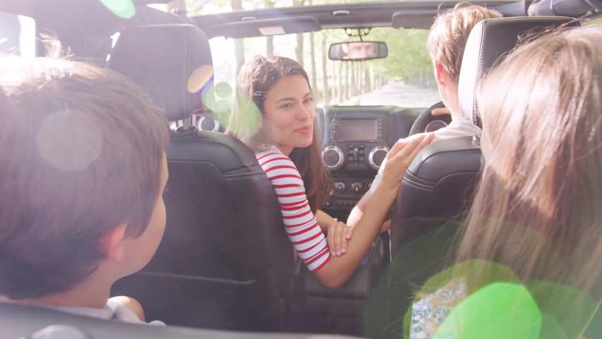Mum turning around to speak to kids in the back of the car