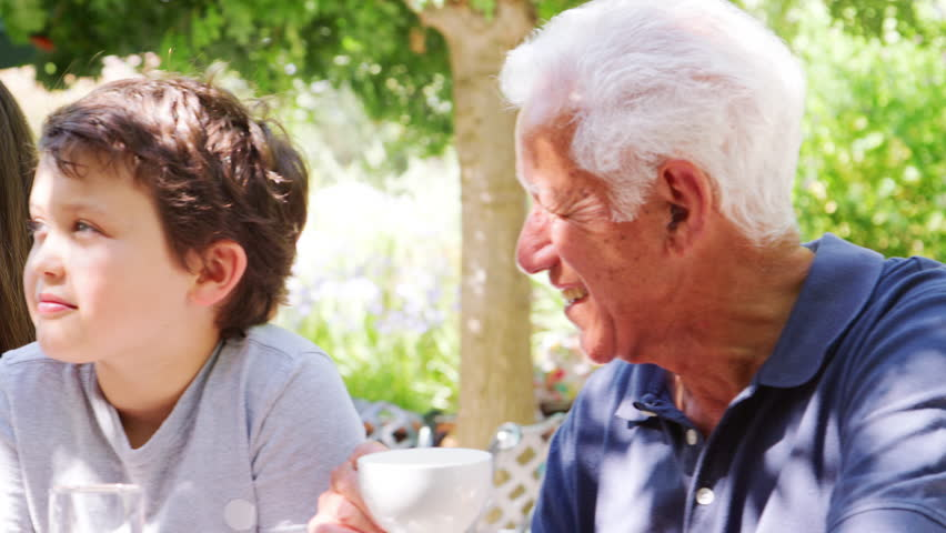 Parents in a park cafe with kids and their grandparents