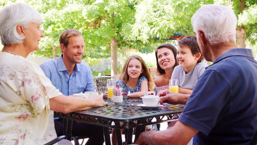Two kids at an outdoor cafe with parents and grandparents