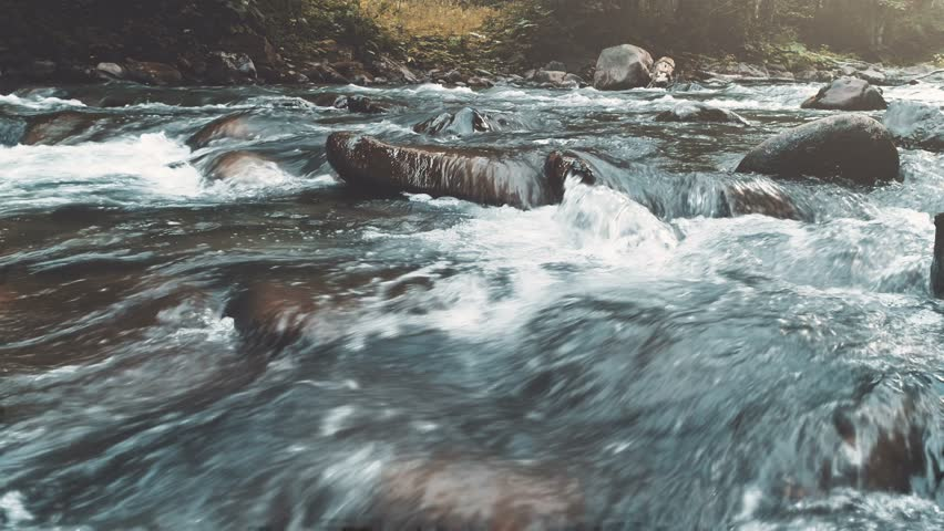 Mountain river in autumn forest. Water Slow Motion flows through massive boulders. Nature, travel, hiking, holidays concept. Dark vintage toning filter. Carpathian mountains, Ukraine, Europe. 4k | Shutterstock HD Video #1012449647