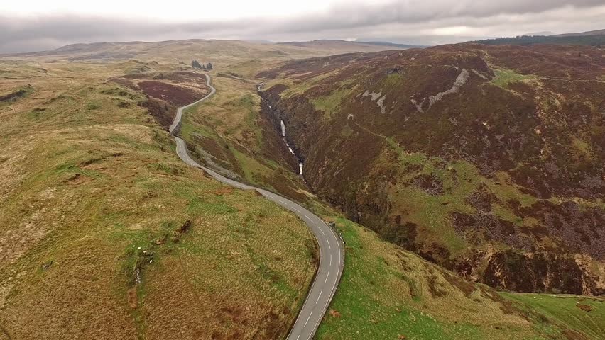 Aerial view of the B4391 through the moor and mountains of Wales close to waterfall, Snowdonia - United Kingdom