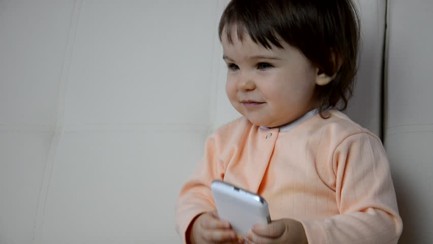 Adorable toddler boy sitting on the sofa in the living room and playing with smartphone. Child learning how to use smartphone. Boy texting on the phone. - technology and lifestyle concept | Shutterstock HD Video #1012469759