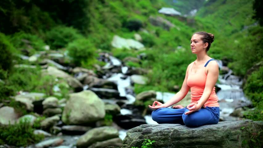 Young sporty fit woman doing yoga - meditating in Padmasana (Lotus Pose) outdoors at tropical waterfall. Himachal Pradesh, India   Shutterstock HD Video #1012469852