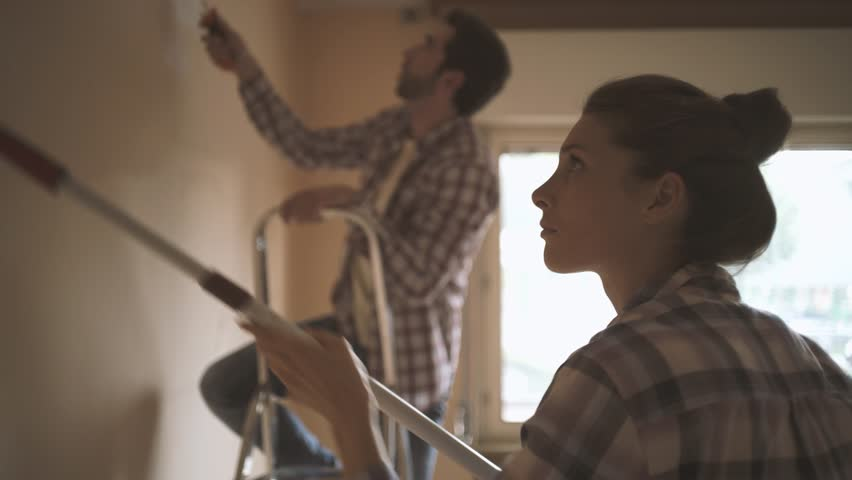 Happy couple renovating their new house and painting interior walls together: lifestyle, home makeover and remodeling concept #1012476371