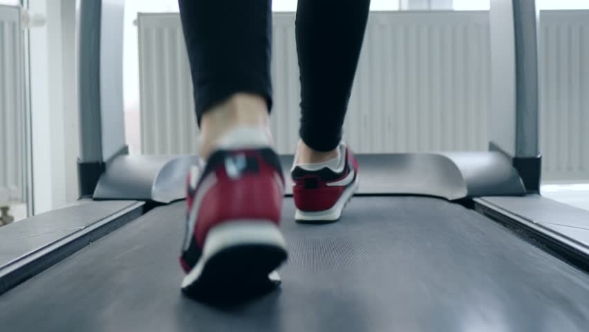 Treadmill, man feet in sports shoes on simulator in gym close-up | Shutterstock HD Video #1012485491