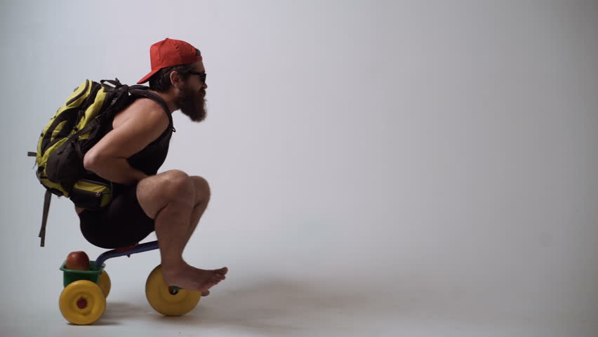 Delivery service. Not baby delivery. A funny bearded man is riding a children's bicycle. | Shutterstock HD Video #1012500056