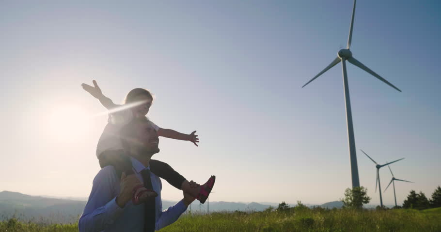 A father engineer, holds his daughter in his arms and runs between the wind turbines with great freedom. Concept of: environmental engineering, renewable energy and love for nature and for the family #1012504949