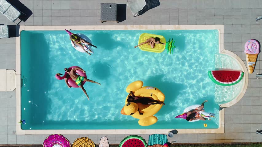 Group of friends having fun in the swimming pool with inflatable colored toys