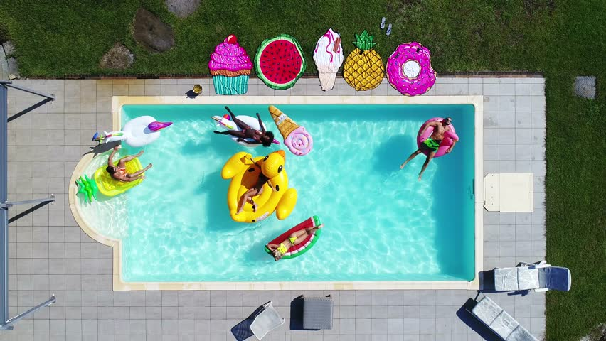Group of friends having fun in the swimming pool with inflatable colored toys | Shutterstock HD Video #1012507055