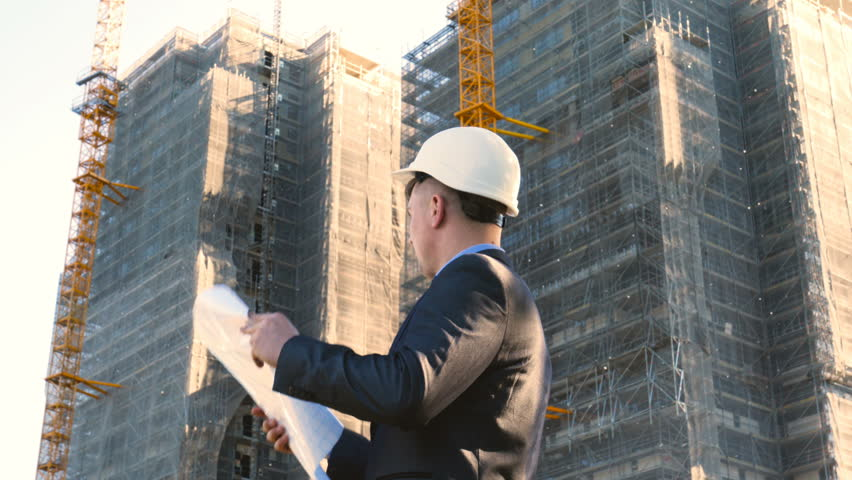 Portrait of a successful young handsome engineer, architect, builder, businessman, wearing a white helmet, in a suit, holding a project in his hand, a skyscraper background and a construction site. | Shutterstock HD Video #1012510889