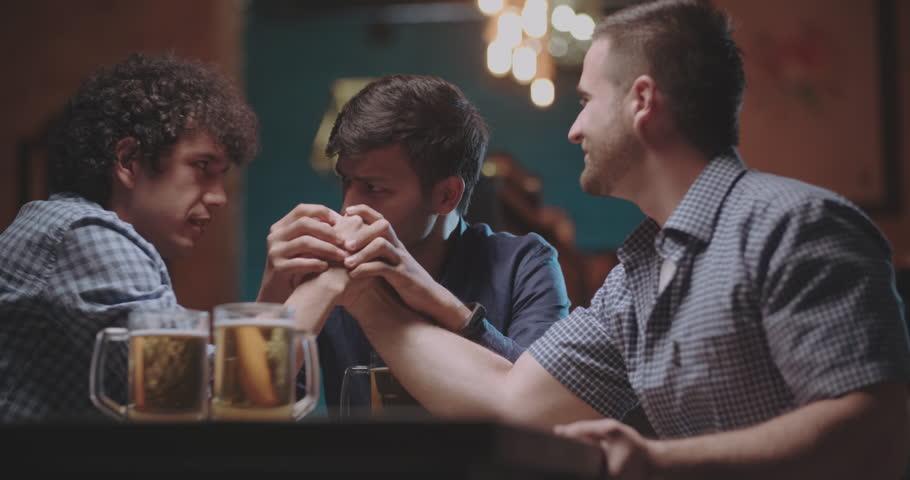 good friends doing armwrestling in pub 4k dollyshot