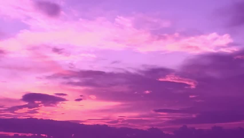 Clouds with orange, purple and black colors at sunset sky. Telephoto video of dramatic pink and purple clouds at sunset. 4K. #1012520081