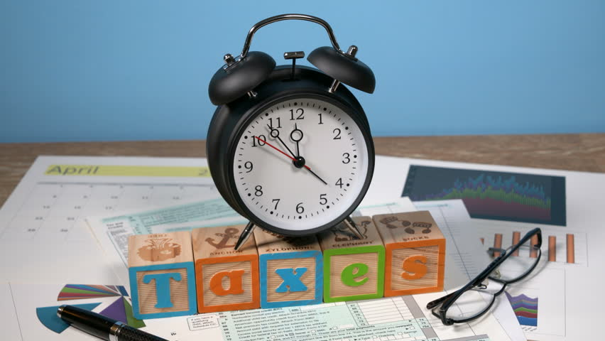 Alarm clock approaching midnight on tax day and taxation forms not completed Royalty-Free Stock Footage #1012522445