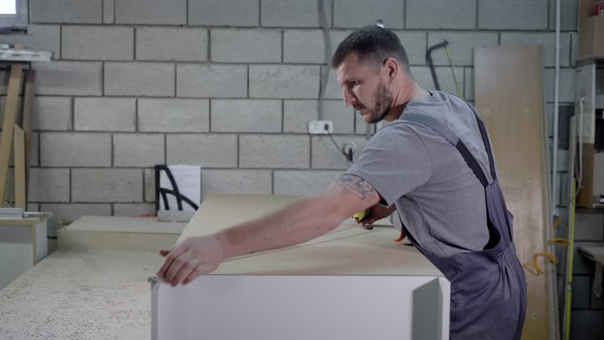 Male worker taking measurements of a big bookshelf in a workshop. #1012530926
