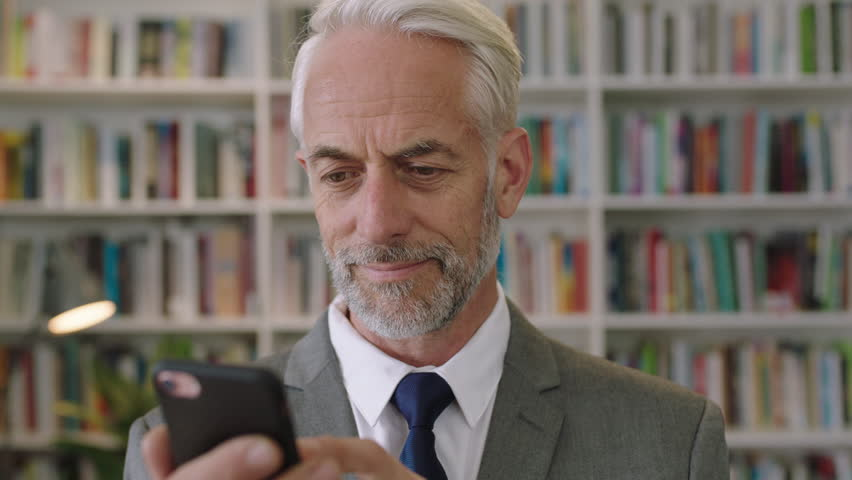 Portrait of professional businessman using smartphone in library office smiling gentleman architect professor lecturer messaging | Shutterstock HD Video #1012537388