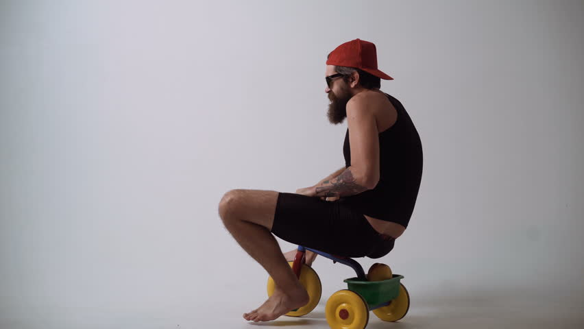 Delivery service. Not baby delivery. A funny bearded man is riding a children's bicycle. | Shutterstock HD Video #1012537511