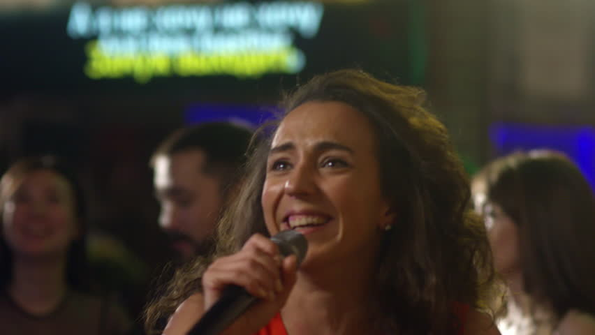 Close up face of smiling attractive woman jumping and singing into microphone when enjoying herself in karaoke bar with group of multi ethnic friends