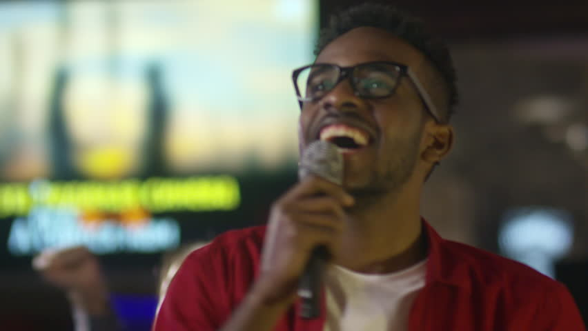 Tilt up shot of joyous black man in glasses looking at song lyrics on screen, smiling and singing into microphone when partying with friends in karaoke bar
