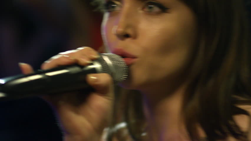 Extreme close up of young female singer dancing to music and using microphone when performing at party | Shutterstock HD Video #1012550063