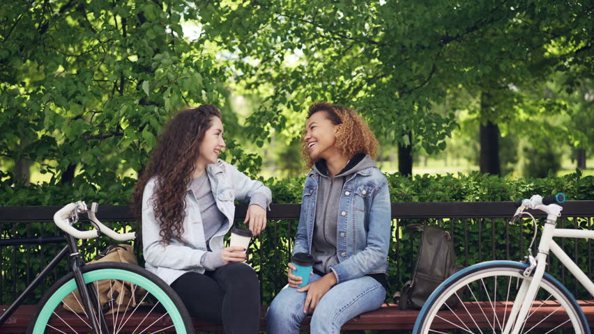 Attractive young women Caucasian and African American are chatting and drinking takeaway coffee while sitting on bench in park and resting after riding bikes.   Shutterstock HD Video #1012550276
