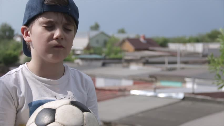 7 year-old Russian white boy in cap with closed eyes and a soccer ball in his hands praying for football team on the background of provinicial Russian urban city garages. Football children education | Shutterstock HD Video #1012552907
