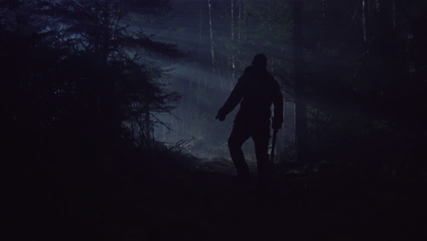 CREEPY MAN WALKS THROUGH DARK FOREST WITH AXE