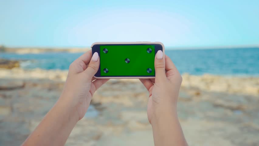 Close up of woman hands holding and using horizontal smartphone device with green screen against sea shore while standing on the beach on vacation. Chroma key. Tracking motion