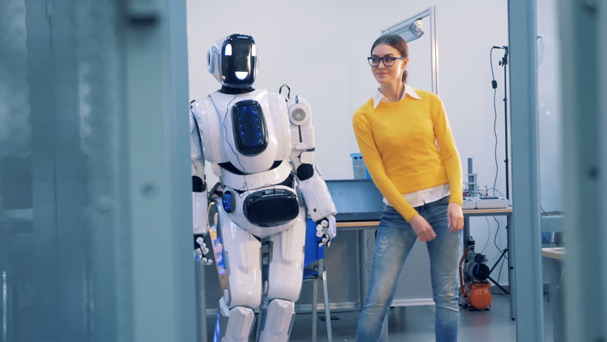 Robot and human relations. A cyborg spanks a woman, while dancing, then she slaps its face and leaves. 4K. Royalty-Free Stock Footage #1012566989