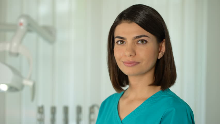 Charming female doctor posing for camera, confidence and professionalism, clinic