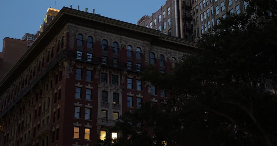 A nighttime establishing shot (NX) of a typical red brick apartment or office building in midtown Manhattan, New York. Day/Night matching available.  Day ID: 1012671602