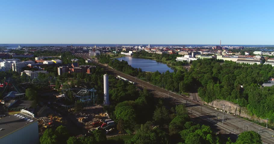 Train in a city, C4k aerial tracking view following a train leaving the railway station, in Helsinki, on a sunny summer morning dawn, in Helsingfors, Uusimaa, Finland | Shutterstock HD Video #1012584713