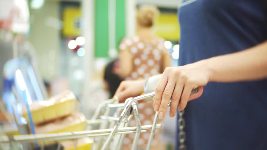 The buyer woman is waiting in line at the cashier in the mall. background blur. 4k